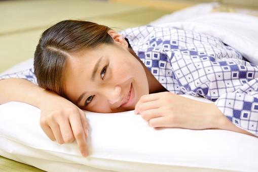 屋内 人物 日本人 1人  大人  女性 20代 温泉施設 宿泊施設 ホテル 旅館 温泉 和風 寝具 布団 ふとん 枕 まくら うつ伏せ 俯せ 腹這い 浴衣 ゆかた 和服 着物 目覚め 起床 朝 微笑む 笑顔 見る 見つめる かわいい mdjf013 OSCouple