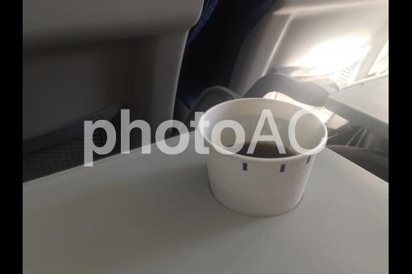 飛行機の座席とコーヒーの写真