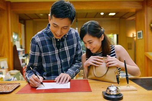 屋内 人物 日本人 2人 大人 20代 30代 男性 女性 夫婦 カップル 旅行 旅館 ホテル 受け付け 受付 チェックイン 記入 書く ペン 筆記具 持つ  カウンター 見る 楽しみ 上半身寄り添う  mdjm001 mdjf013 温泉 温泉旅行 OSCouple