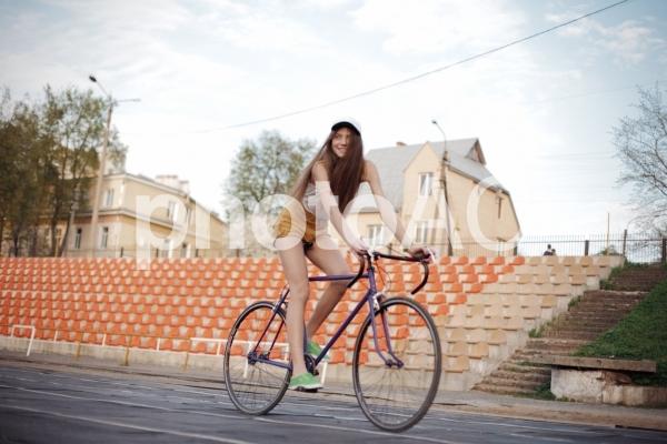 競技場で誰もいない観客席の前を自転車に乗って通過する白い帽子を被った若い女性の写真