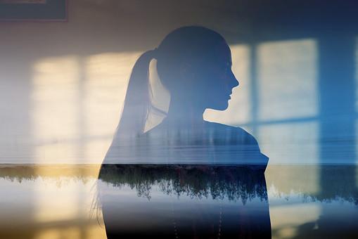 窓に映る景色と女性のシルエットの写真