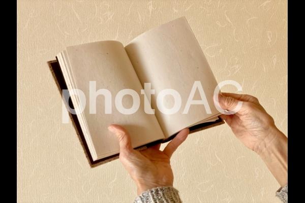本のページをめくる高齢者の手の写真