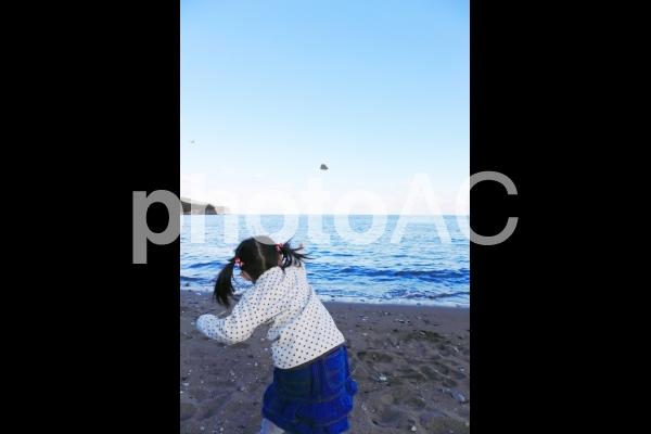 海に石を投げる少女の写真