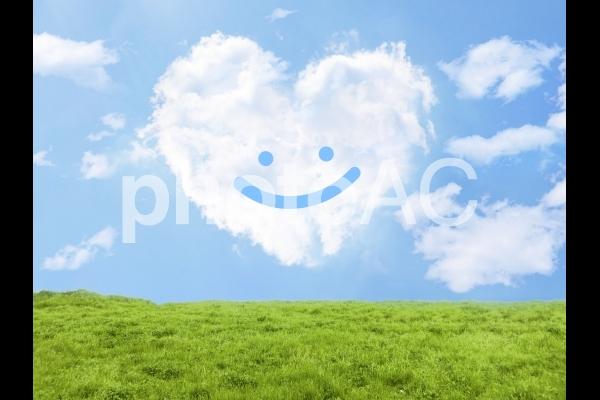 笑顔とハート型雲と草原の写真