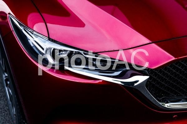 自動車のヘッドライト写真(MAZDA 新型CX-5)。高級感漂う深い赤色が印象的な画像。の写真