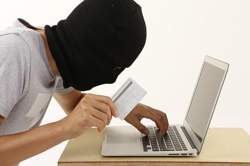 人物 ネット犯罪 パソコン PC ノートパソコン ハッカー ハッキング サイバー攻撃 ネット 書き込み  パスワード なりすまし フィッシング インターネット セキュリティ 違法行為 犯罪 犯人 犯罪者  アクセス 不正アクセス 個人情報 流出 漏えい カード クレジットカード 不正使用 覆面 白バック 白背景 プライバシー 目出し帽 マスク