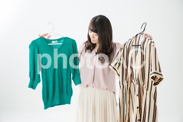 洋服選びに困る女性の写真