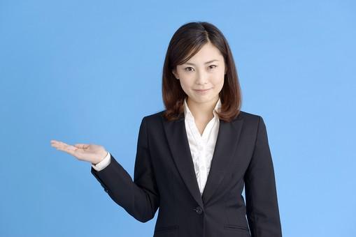 人物 女性 日本人 20代 若者  ビジネス スーツ 黒 紺色 セミロング  OL 社会人 会社員 ビジネスマン 就活  就職活動 真面目 ポーズ 屋内 スタジオ撮影  ブルーバック 上半身 案内 説明 誘導 おすすめ 横 コピースペース 笑顔 mdjf013