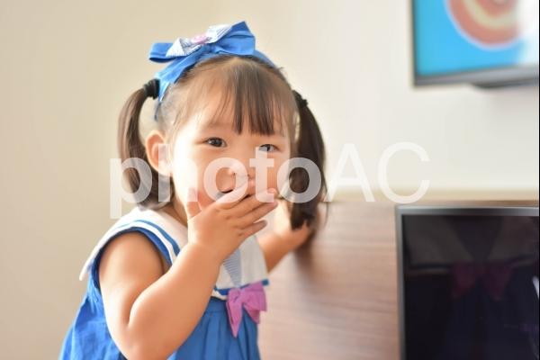 口をおさえる子供の写真