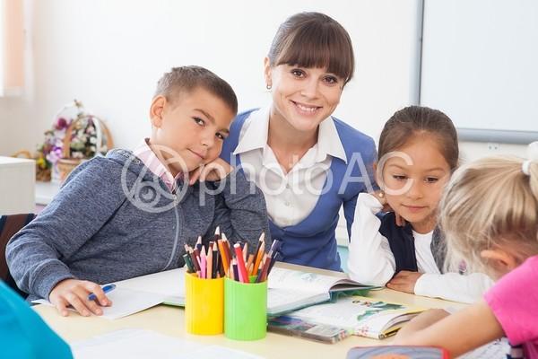一つの机で勉強する小学生と先生6の写真