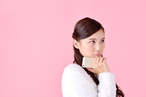 人物 女性 日本人 若者 若い  20代 美人 かわいい ロングヘア カジュアル  ラフ 私服 セーター ニット 屋内  スタジオ撮影 背景 ピンク ピンクバック ポーズ  おすすめ 上半身 スマホ スマートフォン 携帯 電話 持つ 悩む 考える 困惑 mdjf007