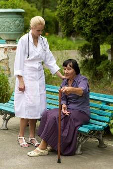 屋外 野外 外 病院 庭 公園 ベンチ 外国人 老人 高齢者 女性 おばあさん おばあちゃん 患者 女医 白人 金髪 白衣 医師 医者 スカート 座る 杖 つえ 突く つく 持つ 寄り添う 立つ 見守る mdfs016 mdff142