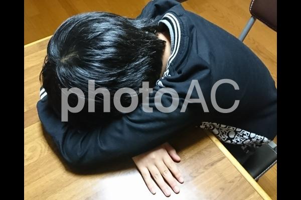 机にうずくまって泣く子供。の写真