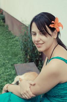 外国 海外 屋外 人物 1人 外国人 白人 セルビア人 大人 若い 女性 女 女の子 ブルネット 黒髪 セミロング まとめ髪 ひっつめ髪 無造作ヘア 普段着 青緑の服 ノースリーブ キャミソール ネックレス ペンダント レザーコード ブレスレット アクセサリー 髪飾り 花飾り 花 ユリ ゆり 白壁 ベンチ 椅子 動物 猫 ネコ ねこ 薄茶 植え込み 雑草 見つめる 微笑む 微笑 笑顔 笑う mdff021