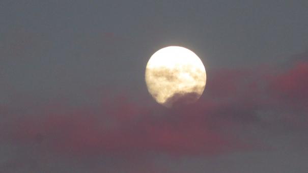 夕陽に染まる雲と月の写真