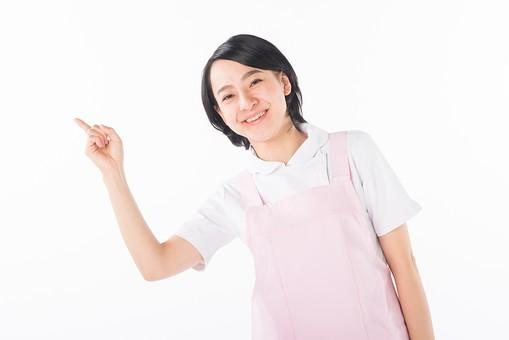 女性 おんな 女 エプロン 白衣 ピンク  介護 介護士 介助 ナース 病院  ヘルパー 看護師  手 ポーズ 指 人差指 人差し指 指す  手   白 白背景 白バック 爽やか 優しい 穏やか 笑顔 微笑み 注目 案内 mdjf017