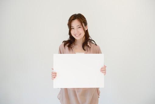 日本人 女性 女 30代 アラサー グレーバック 背景 グレー ポーズ ハーフアップ 髪型 茶髪 ナチュラル 私服 カジュアル ピンク ピンクベージュ 紙 画用紙 ホワイトボード 白 白紙 見せる アピール 持つ スマイル 笑顔 mdjf013