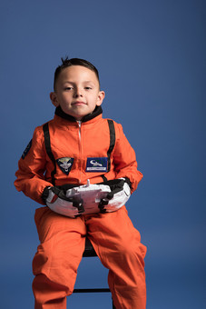 背景 ダーク ネイビー 紺 男の子 男子 男児 男 子ども こども 子供 1人 ひとり 一人 児童 宇宙服 宇宙 服 スペース スペースシャトル 宇宙飛行士 飛行士 オレンジ 希望 夢 将来 未来 体験 職業体験 職業 小道具 小物 おもちゃ コントローラー リモコン コントロール 座る 腰かける 正面 外国人  mdmk009
