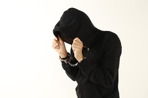 人物 男性 フード 黒ずくめ 犯罪 犯行 犯人 犯罪者 容疑者 現行犯 事件 逮捕 捕まる 捕まえる 手錠 顔を隠す 俯く うつむく 下向く うなだれる 横向き 上半身 アップ 白バック 白背景