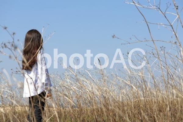 枯れた草原に立つ少女の写真