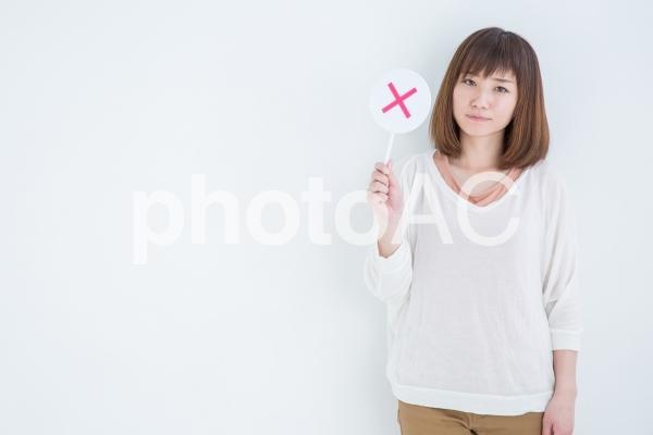 バツを持つ女性の写真