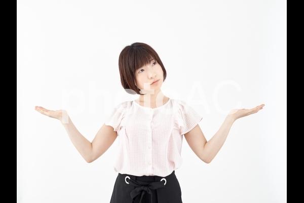 両手を上げ比較する女性(困り顔)の写真