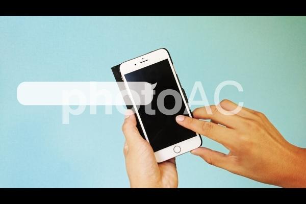 スマホを操作する人差し指と吹き出し_青背景の写真