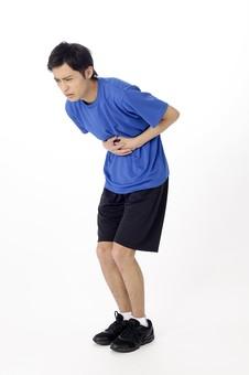 全身 人物 人 男性 男 大人 日本人 20代 スタジオ撮影 白背景 白バック Tシャツ 青 手 両手 腹 胃 腹部 押さえる 腹痛 胃痛 痛み 痛い さしこみ 吐き気 心配事 不調 くの字 苦痛 スポーツ 運動 mdjm025