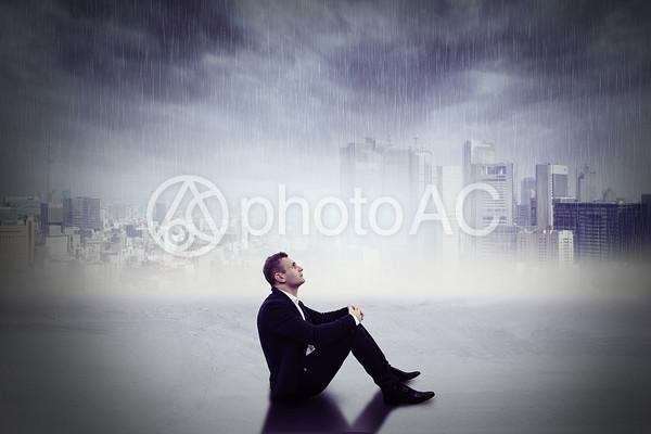 雨の降る都会の風景と三角座りのスーツの男性の写真