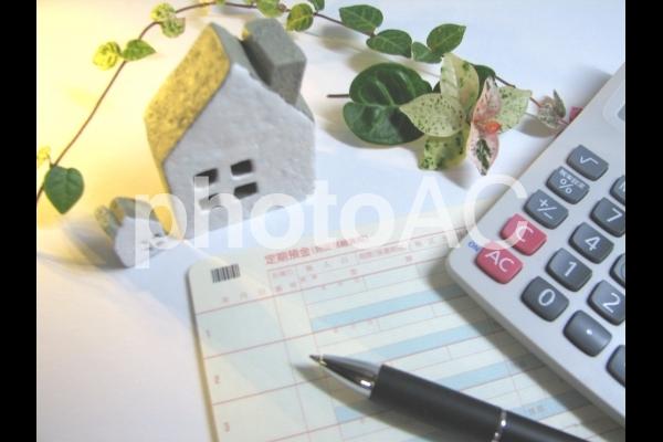 家と電卓 通帳 1 やりくり 節約 不動産 人生設計の写真