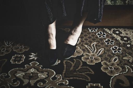 室内 屋内 外国人 老人 高齢者 女性 おばあさん おばあちゃん 座る 腰掛ける スカート 紺色 ネイビー 足元 皺 しわ シワ カーペット 絨毯 寝室 ソファ ベッド 靴 スリッパ 上品