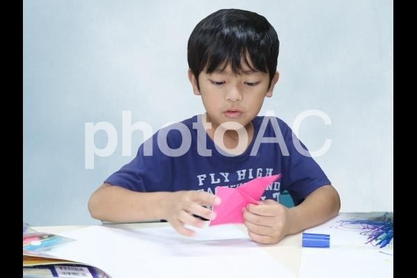 折り紙で遊ぶ男の子の写真