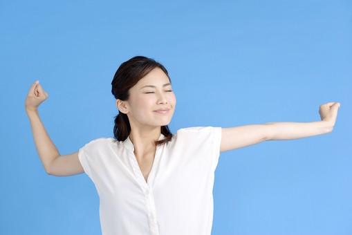 女性 ポーズ 人物 30代 日本人 黒髪 上半身 爽やか カジュアル 屋内 正面 ブルーバック 青背景 半そで 白 笑顔 笑み 微笑 スマイル にこやか 両手 上げる 眠い 寝起き 伸び 背伸び 目 瞑る mdjf013