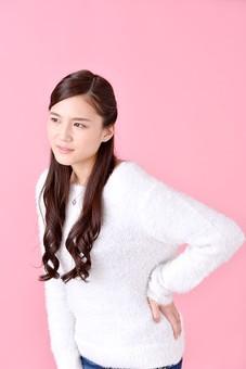 人物 女性 日本人 若者 若い   20代 美人 かわいい ロングヘア カジュアル  ラフ 私服 セーター ニット 屋内  スタジオ撮影 背景 ピンク ピンクバック ポーズ  おすすめ 上半身 腰痛 腰 痛い 体調不良 疲れ 疲労 ぎっくり腰  mdjf007