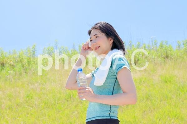 運動の途中で水分補給・汗をぬぐう女性の写真