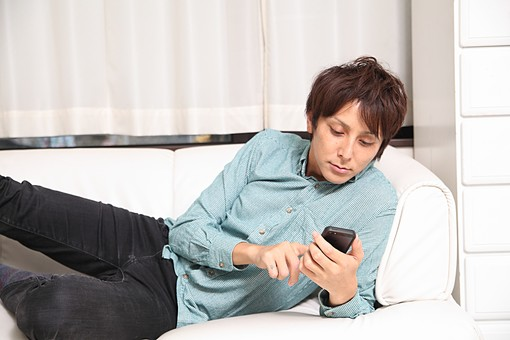 人物 日本人 男性 若者 若い 20代  1人 部屋 室内 屋内 リビング  ソファ 電話 携帯 スマホ スマートフォン  寝そべる 寛ぐ くつろぐ リラックス メール メールチェック LINE 確認 見る 休日 オーバーリアクション  mdjm009