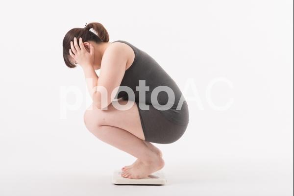 体重計にのり困っている女性1の写真