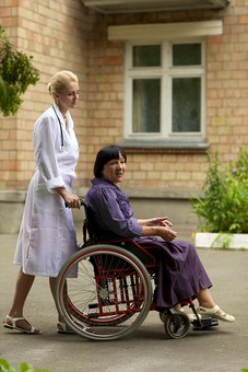 屋外 野外 外 病院 庭 公園 外国人 老人 高齢者 女性 おばあさん おばあちゃん 患者 女医 白人 金髪 白衣 医師 医者 スカート 車椅子 車いす 乗る 座る 押す 散歩 歩く  話す 話しかける 全身 mdfs016 mdff142
