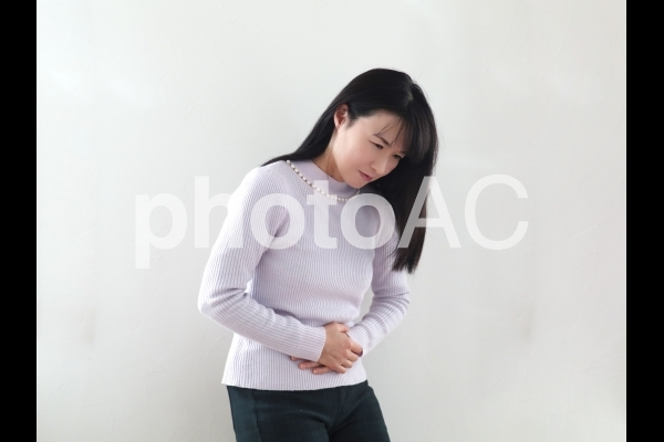 お腹を抑える女性の写真