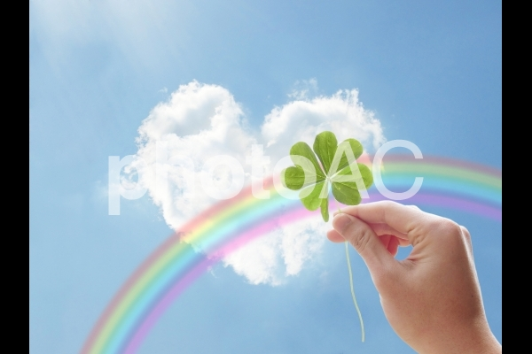 ハート型の雲と青空と虹四つ葉のクローバーを持つ手の写真