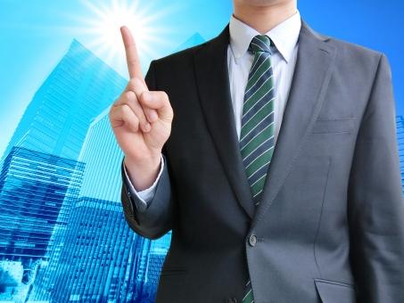 ビジネスのポイントを指し示す男性-ビジネス街背景の写真