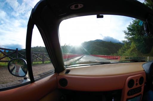 ドライブ オープンカー 車 自動車 運転 山道 爽快 屋根なし 空 青 太陽 逆光 フロントガラス 前方 景色 風景 乗り物 乗物 交通 道 道路 山道 山 走る 走行 旅 旅行 休日 休暇 休み