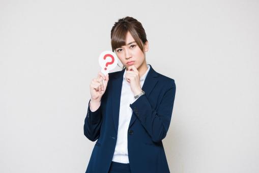 ハテナマークを持つ女性社員の写真