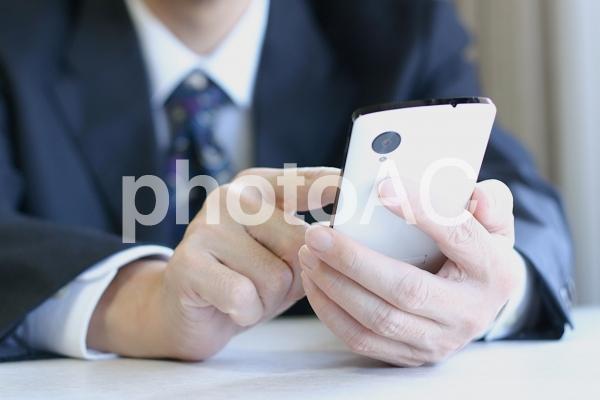 ビジネスマンとスマホ1の写真