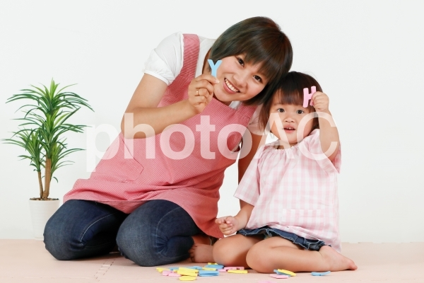 英語の勉強を楽しむ子供と教える女性の写真