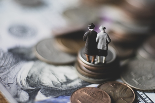 お金の上に立つ高齢者の写真