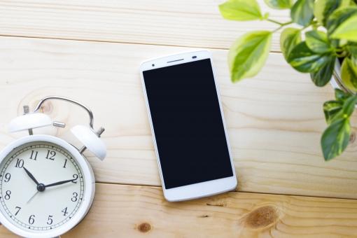 スマートフォンと目覚まし時計の写真
