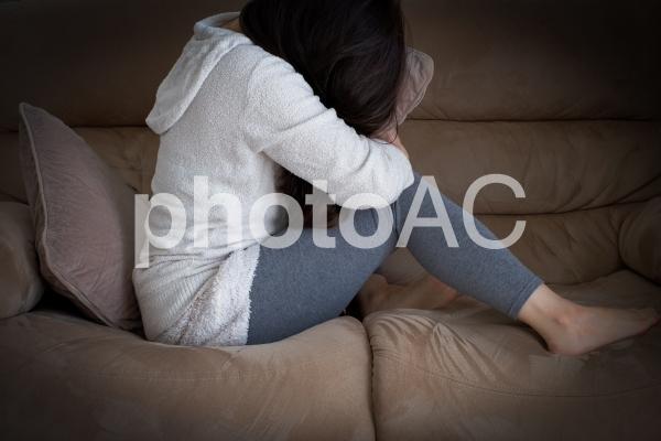 部屋で落ち込む女性 心の健康の写真