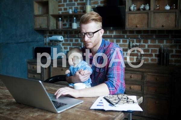 自宅で赤ちゃんを抱っこしながら仕事するお父さん4の写真