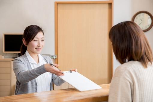 受付で話をする女性の写真